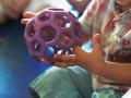 une petite fille découvre une balle spéciale atelier cirque Oreka